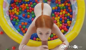 Redhead pulling cock in an inflatable pool
